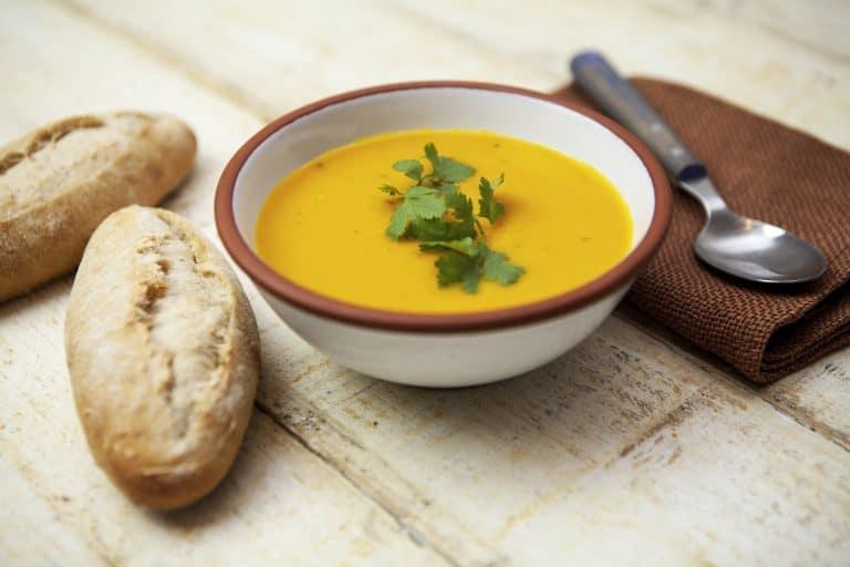 Bild på gul soppa i en skål med bröd och sked bredvid.